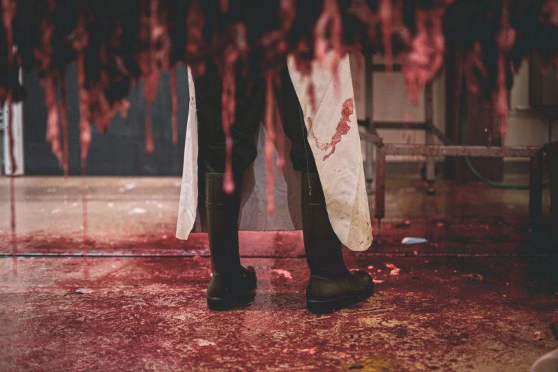 Teurastamon lattia on verinen ja siellä seisoo teurastaja mustissa kumisaappaissa.