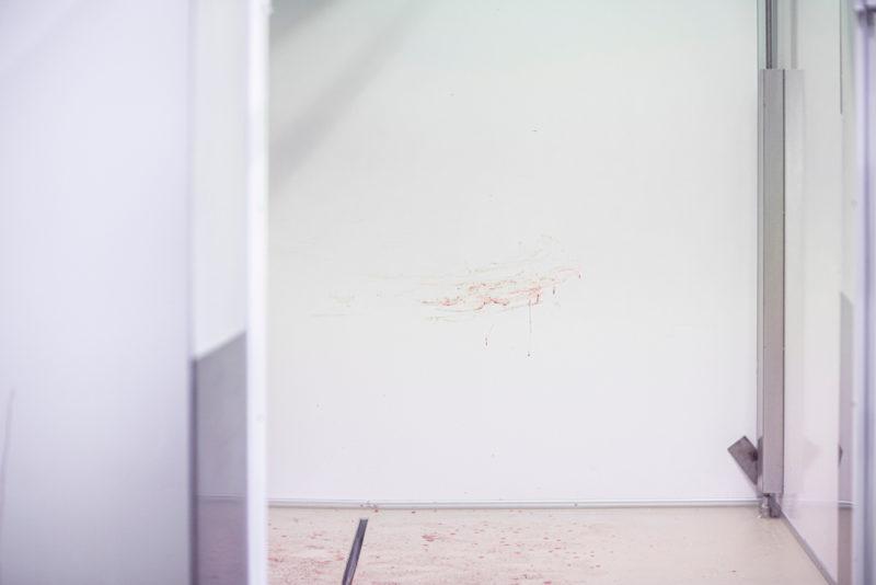 Teurastamon valkoisessa seinässä näkyy tuoreita veriroiskeita.
