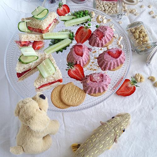 Tarjottimella on kolmioleipiä ja leivoksia.