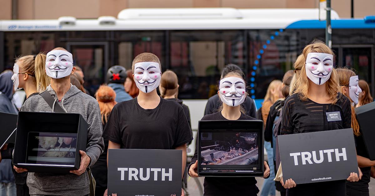 Lähikuva neljästä mielenosoittajasta. He pitävät käsissään joko mustaa kuutiota, joka näyttää videokuvaa eläintiloilta, tai Truth-kylttiä. Aktisivistit käyttävät Guy Fawkes -naamareita, mikä suojelee anonymiteettiä.