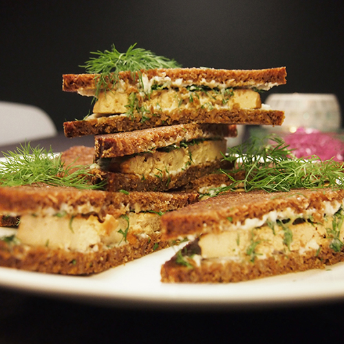 Useita kerrosleipiä aseteltuna lautaselle päällekäin ja koristeltuna tillillä.