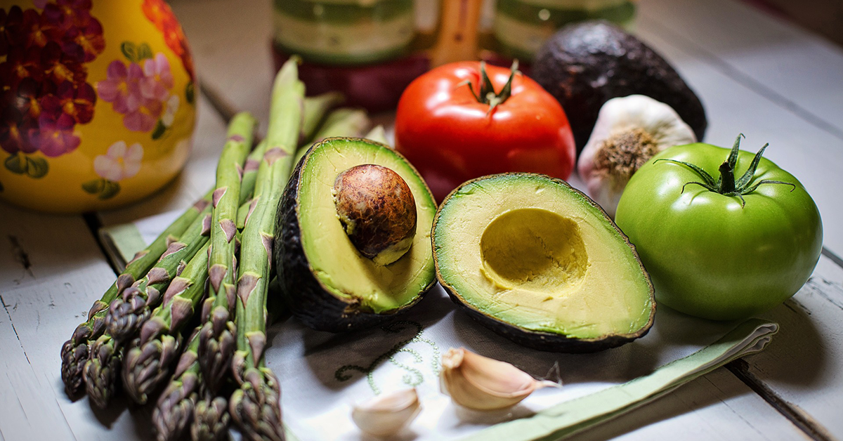 Mikä veganismia vaivaa? Kuvassa parsaa, avokadoja ja tuoreita tomaatteja.