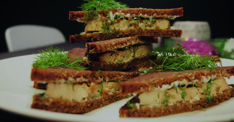 Savutofu-kerrosleipiä lautasella. Koristeena tilliä.