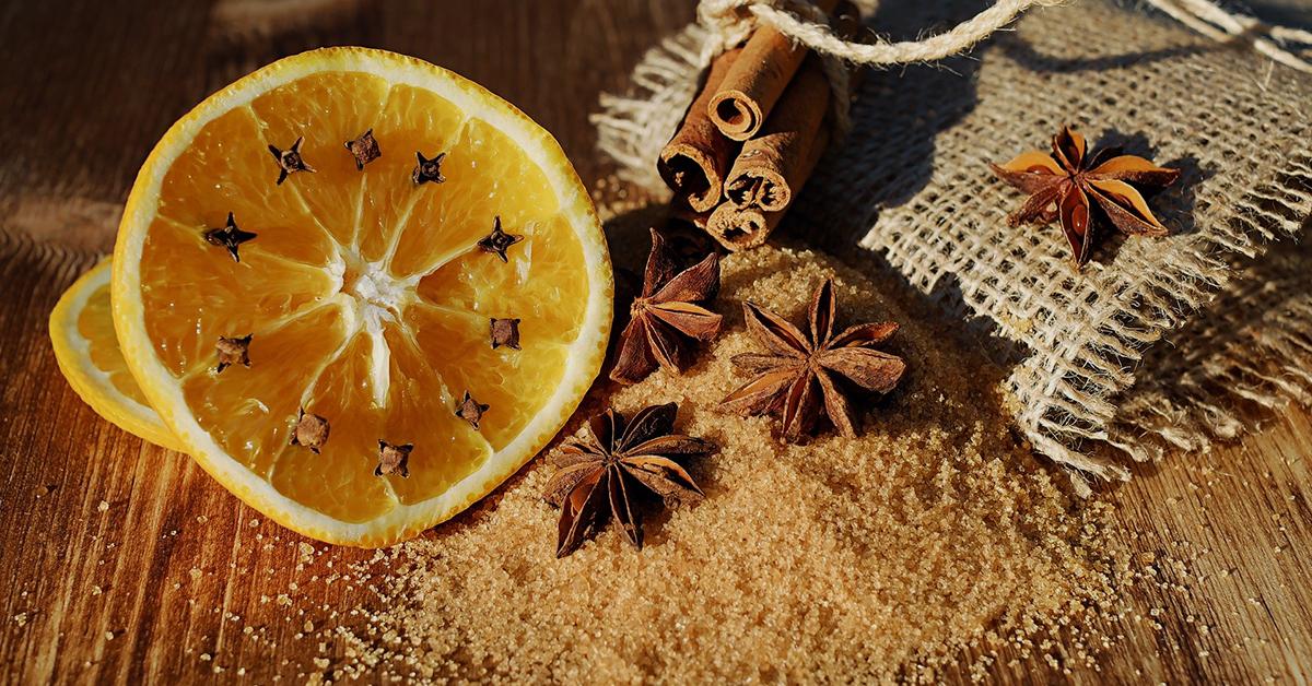 Jouluinen asetelma ruuasta. On appelsiinin siivu, tähtianiksia, tummaa sokeria ja kanelitankoja.