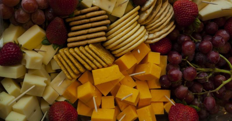 Vegaaniset juustot. Kuvassa juustoa, keksejä ja viinirypäleitä.