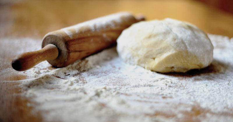 Puukaulin ja taikina jauhoisella pöydällä.