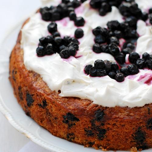 Kakkupohjan päällä on herkullisen näköinen tuorejuustokuorrute. Kakun kruunaa mustikkakoristelu.