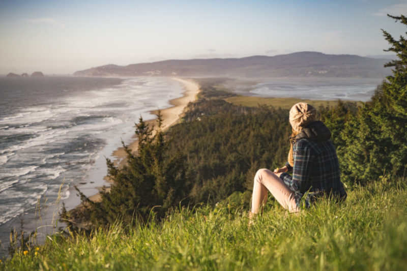 Nainen istuu korkealla rinteellä ja katsoo merta.