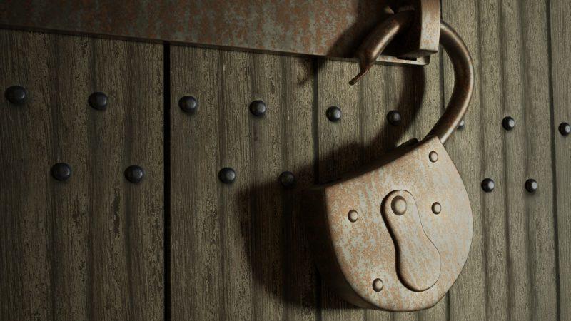 Vanha lukko roikkuu ovessa. Lukko on auki.