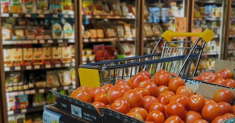 Ostoskärryt supermarketin vihannesosastolla. Etualalla kasa tomaatteja.