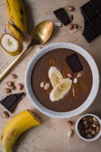 Snickers smoothie tarjotaan banaanin ja suklaan palojen kanssa.