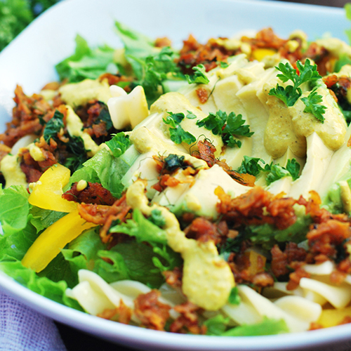 """Vehreä """"tonnikalasalaatti"""" on kasattu lautaselle.   Se on koristeltu tillillä ja persiljalla."""