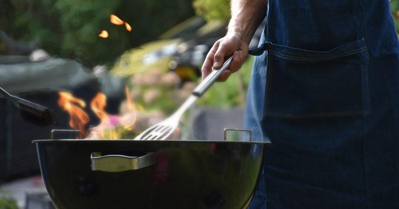 Mieshenkilö grillaamassa pallogrillillä.