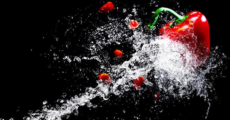 Valokuvaaja on ikuistanut tilanteen, jossa punaiseen paprikaan isketään terävä vesisuihku. Vauhdikas tapahtuma.